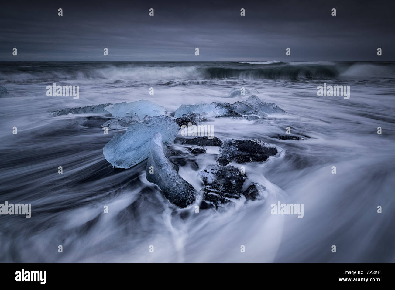 Sea Drifts in around the Icebergs and the Glacial ice that gets swept up on the beach on the black sands at Jokulsarlon, Iceland Stock Photo