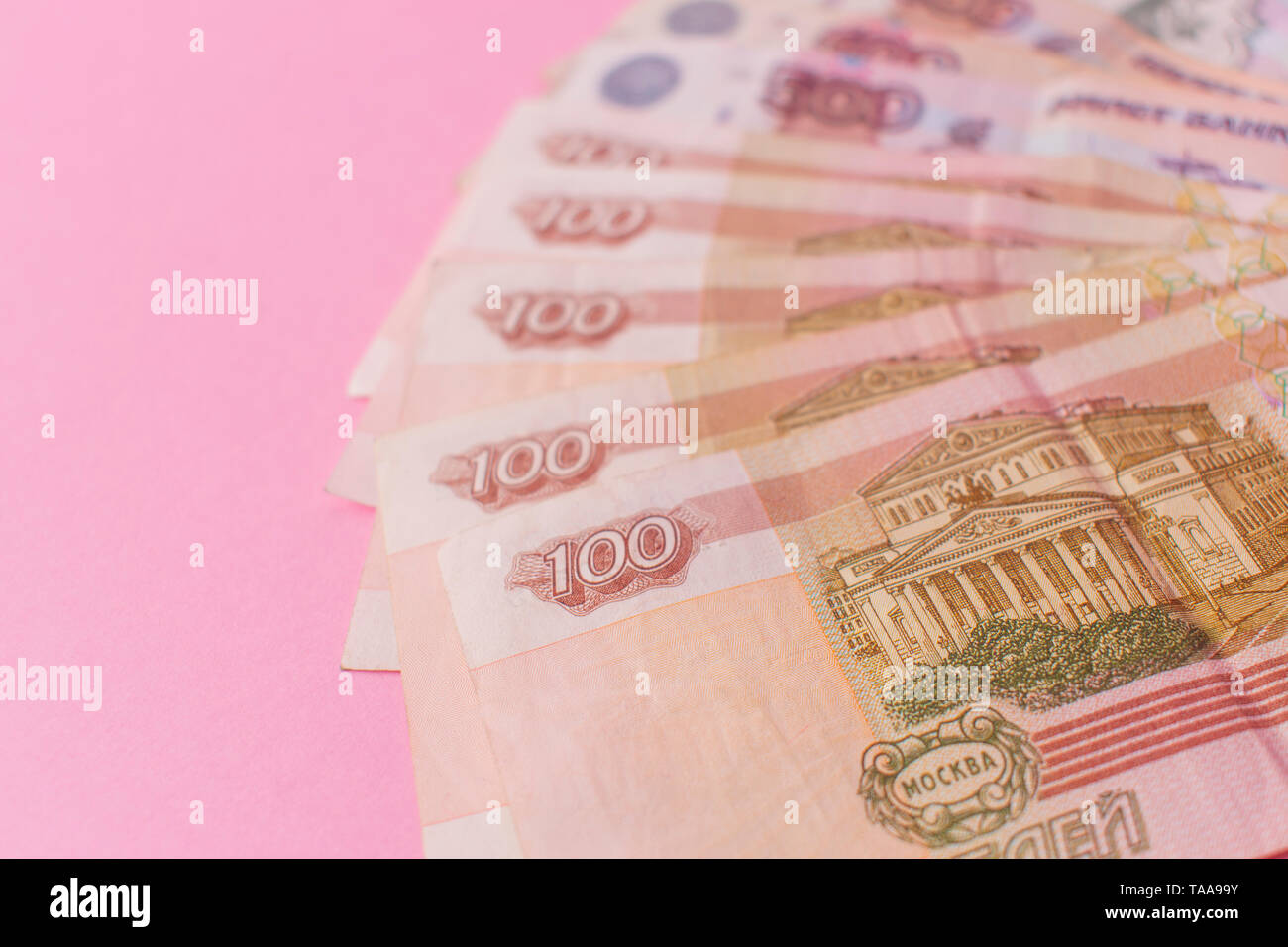 A bundle of Russian money in the form of a fan on a pink background. The concept of poverty, lack of money, poverty. Copy space. Stock Photo
