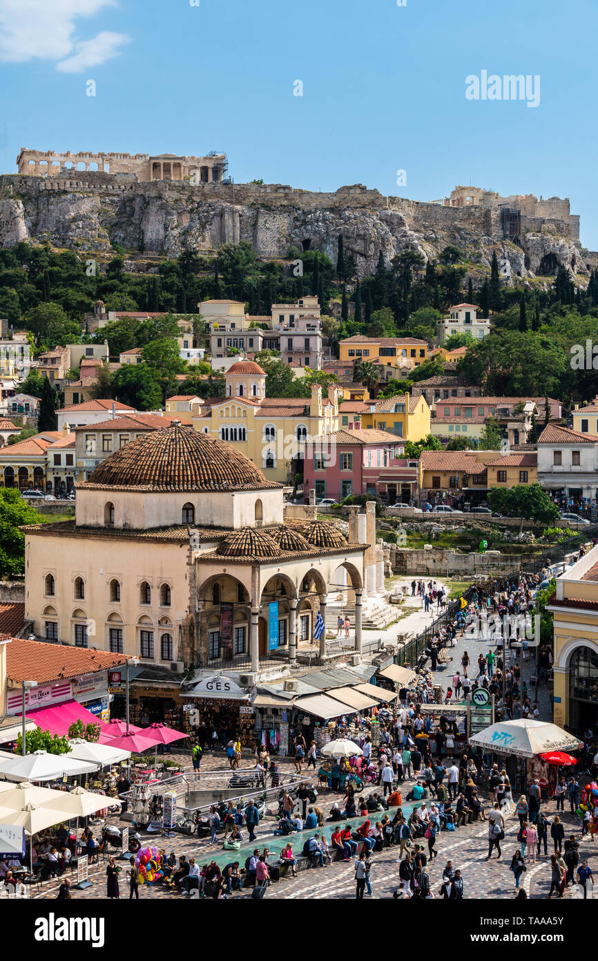 Athens, Greece - May 5 2019: Large crowd wandering around the Monastiraki square in Athens old town with the Acropolis and Parthenon temple on a sunny - Stock Image