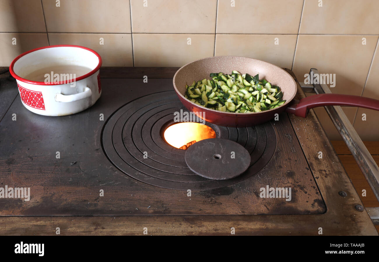 zucchini in a pan are cooked over a stove in a mountain hut - Stock Image