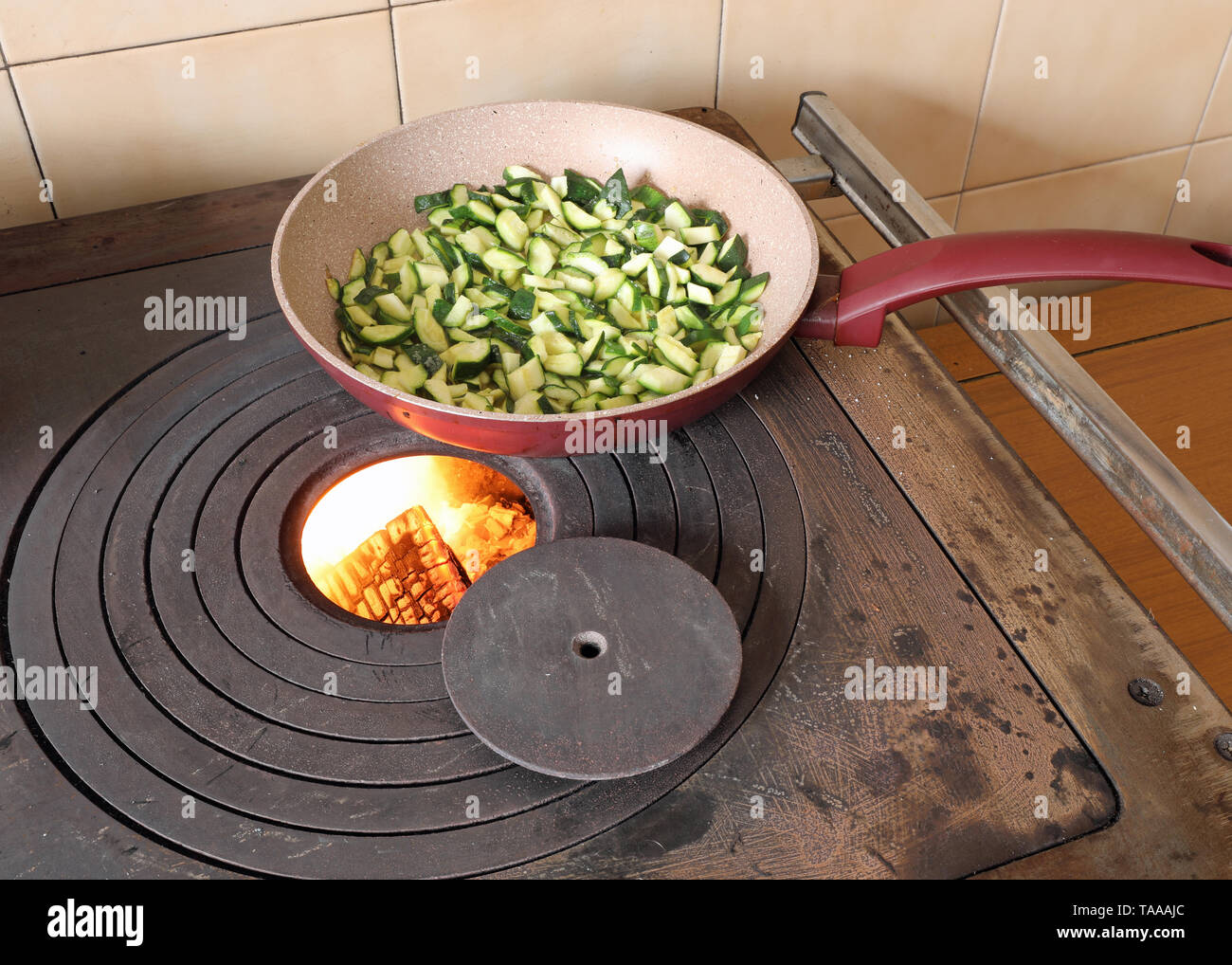 zucchini in a pan are cooked over a wood-burning stove in a mountain hut - Stock Image