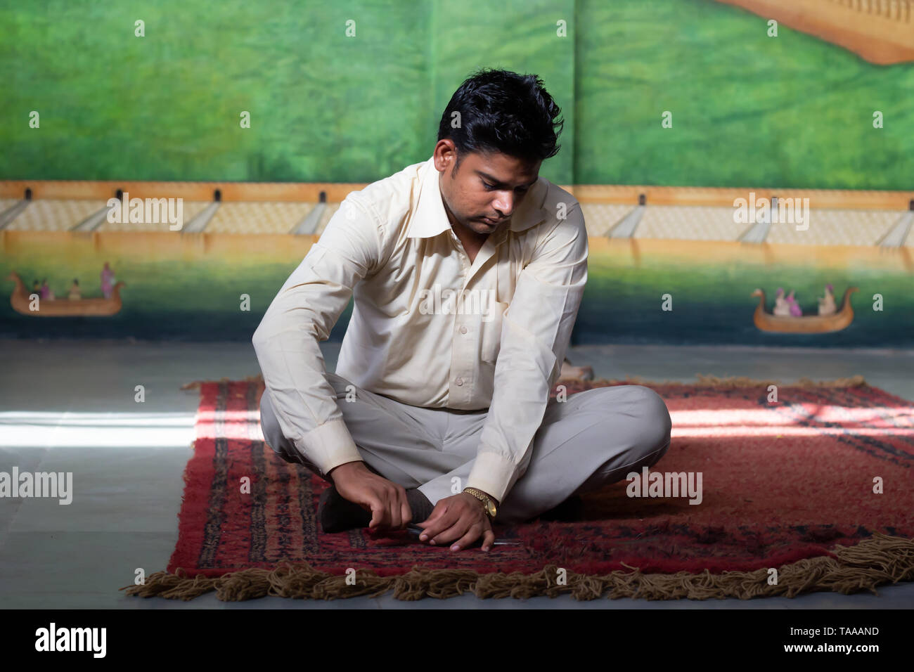 An Indian man working in a rug company cutting off rug tips after hand weaving. - Stock Image