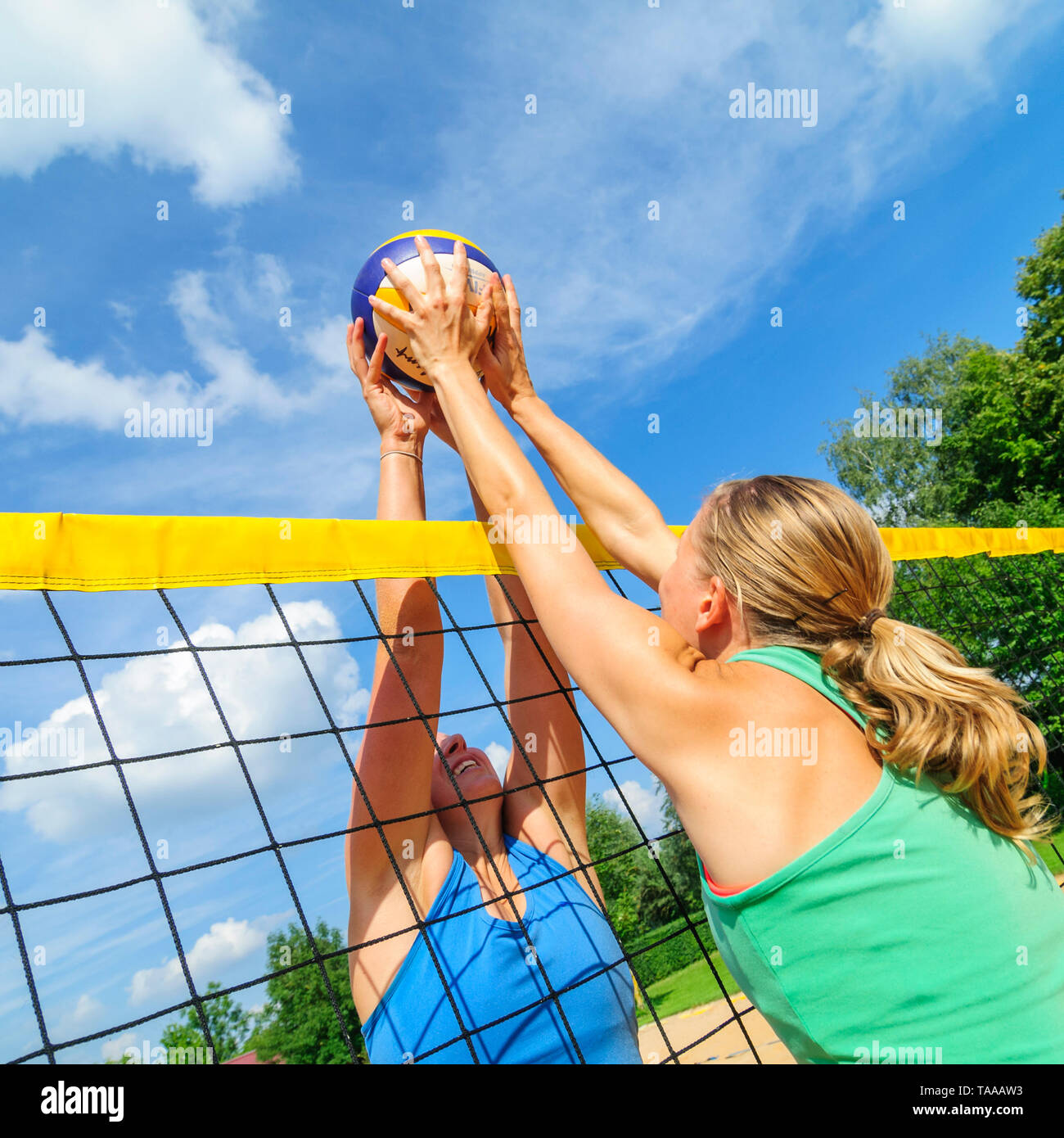 Competitive game on beachvolleyball court at the net - Stock Image
