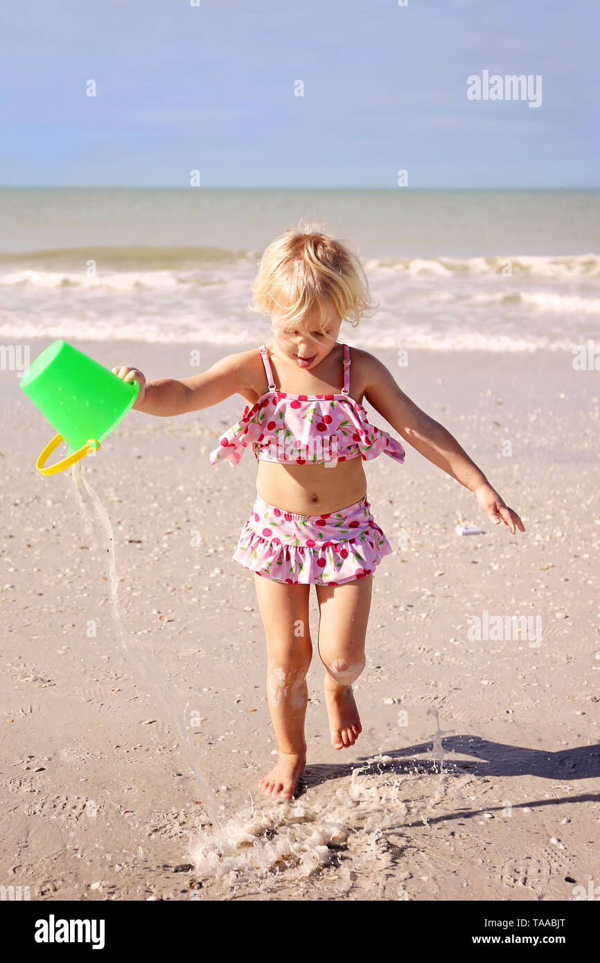 A little kid is running on the beach by the ocean, dumping out a bucket of water in the sand. - Stock Image