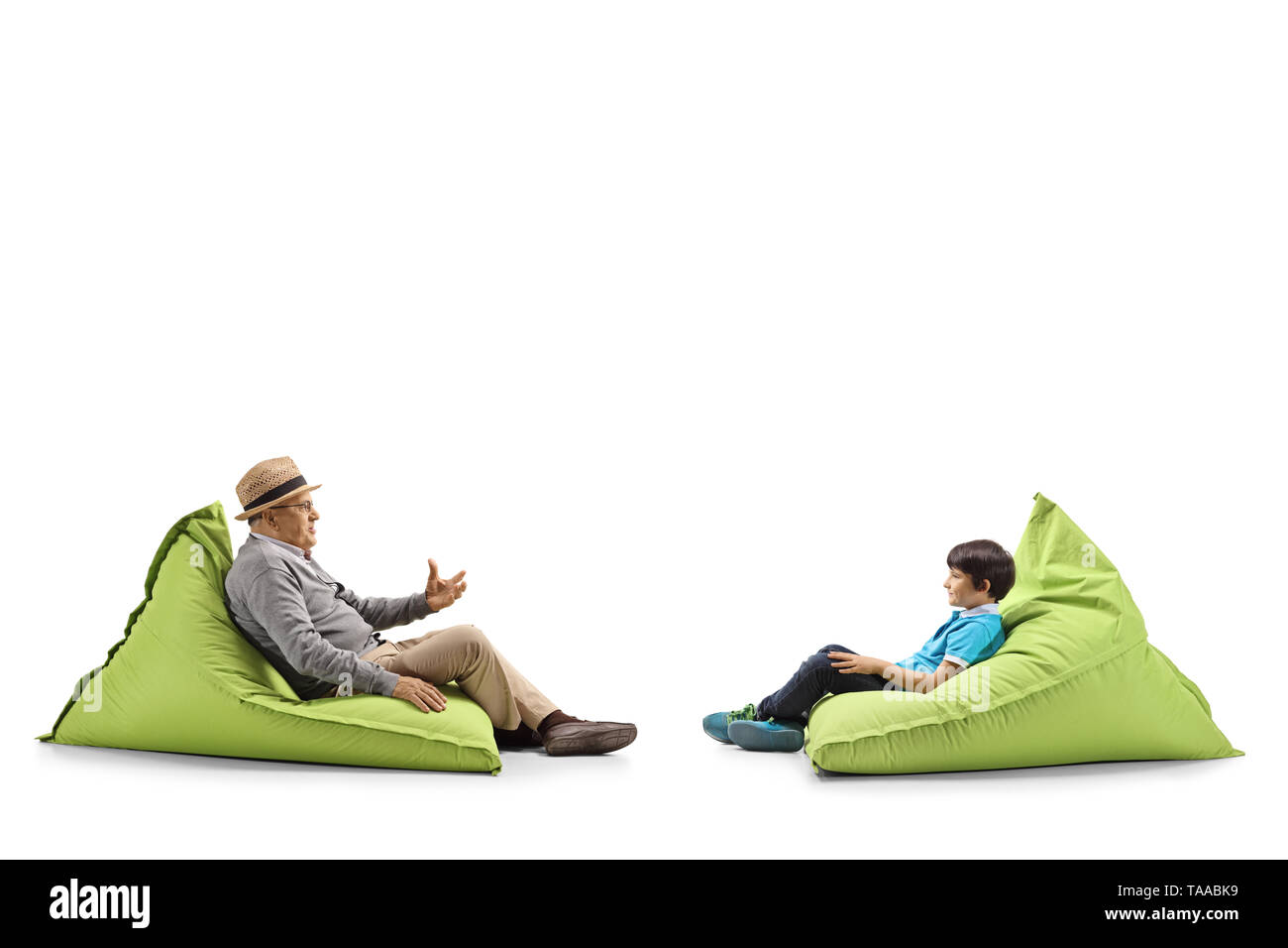 Full length profile shot of a grandfather and grandson sitting on bean bags and talking isolated on white background - Stock Image