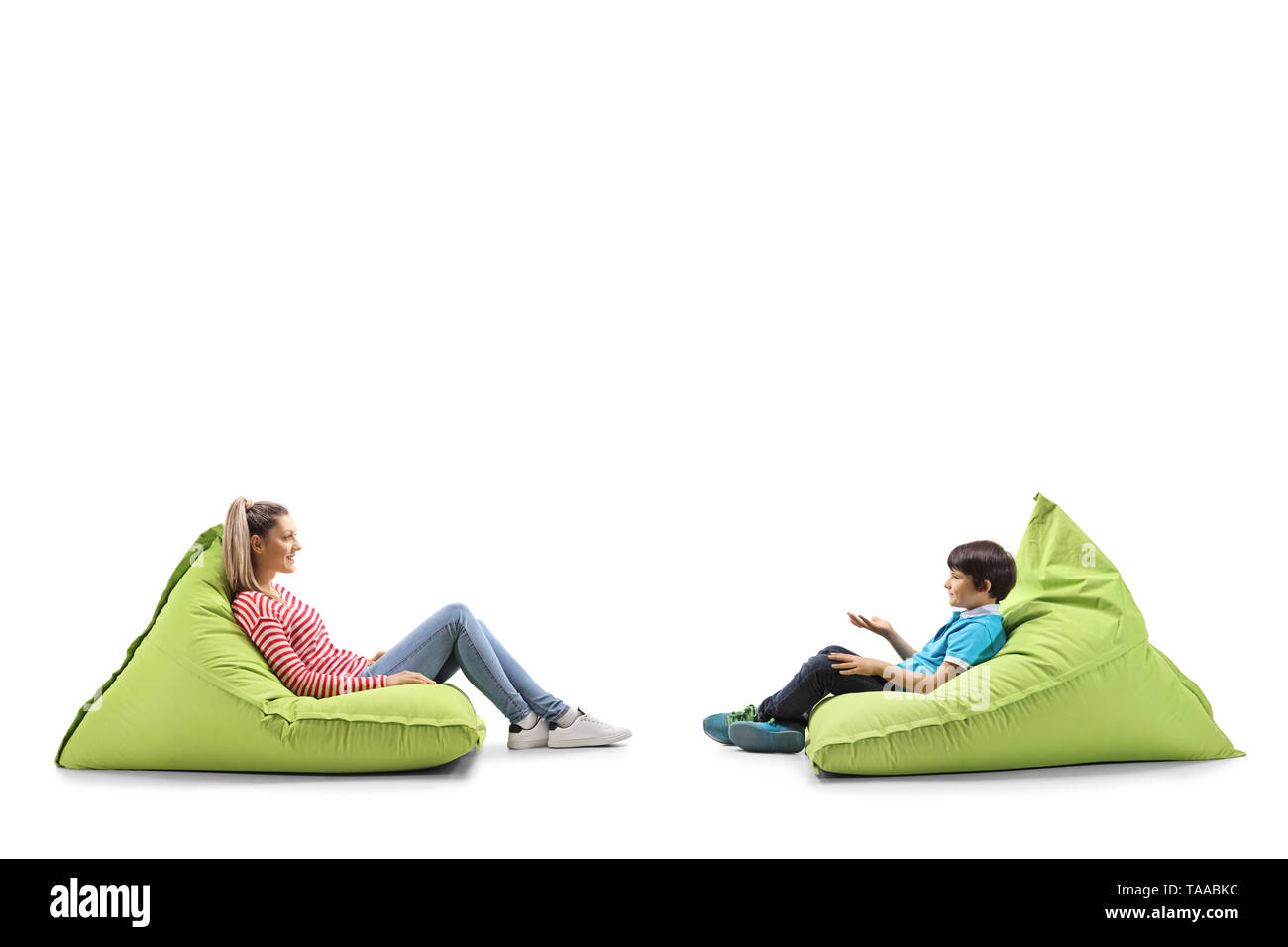 Full length profile shot of a mother and son sitting on bean bags and talking isolated on white background - Stock Image