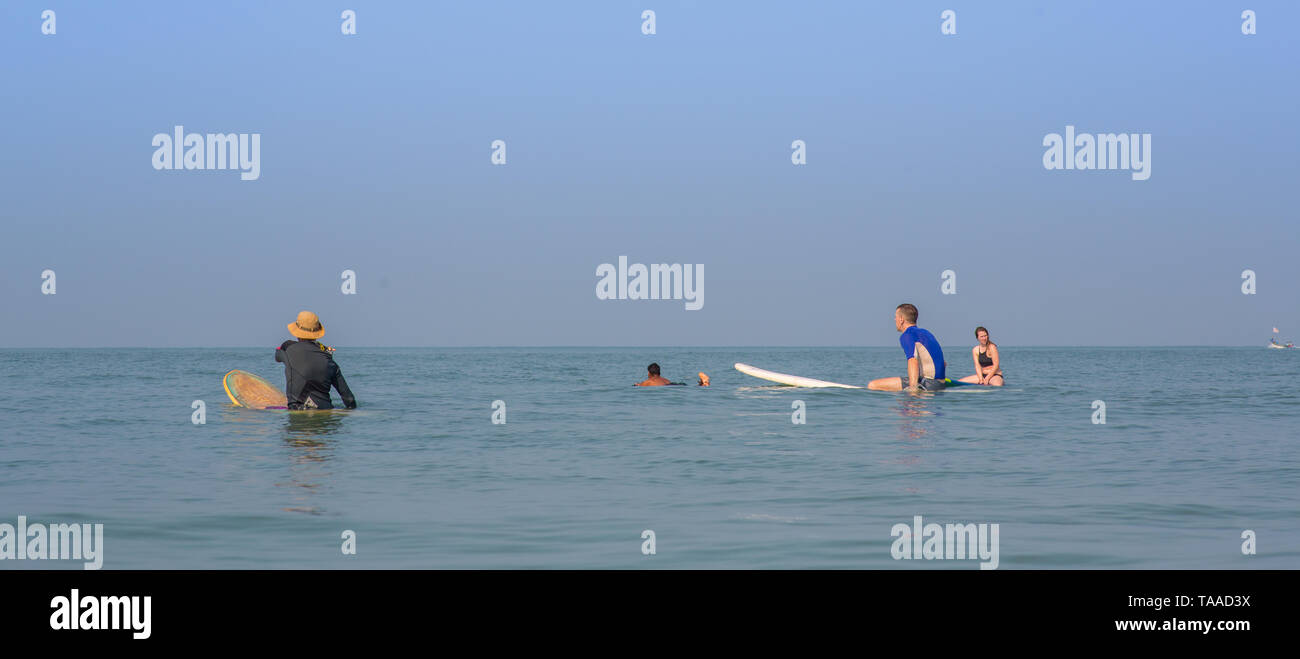 Surfers in the water waiting for waves on a sunny day - Stock Image