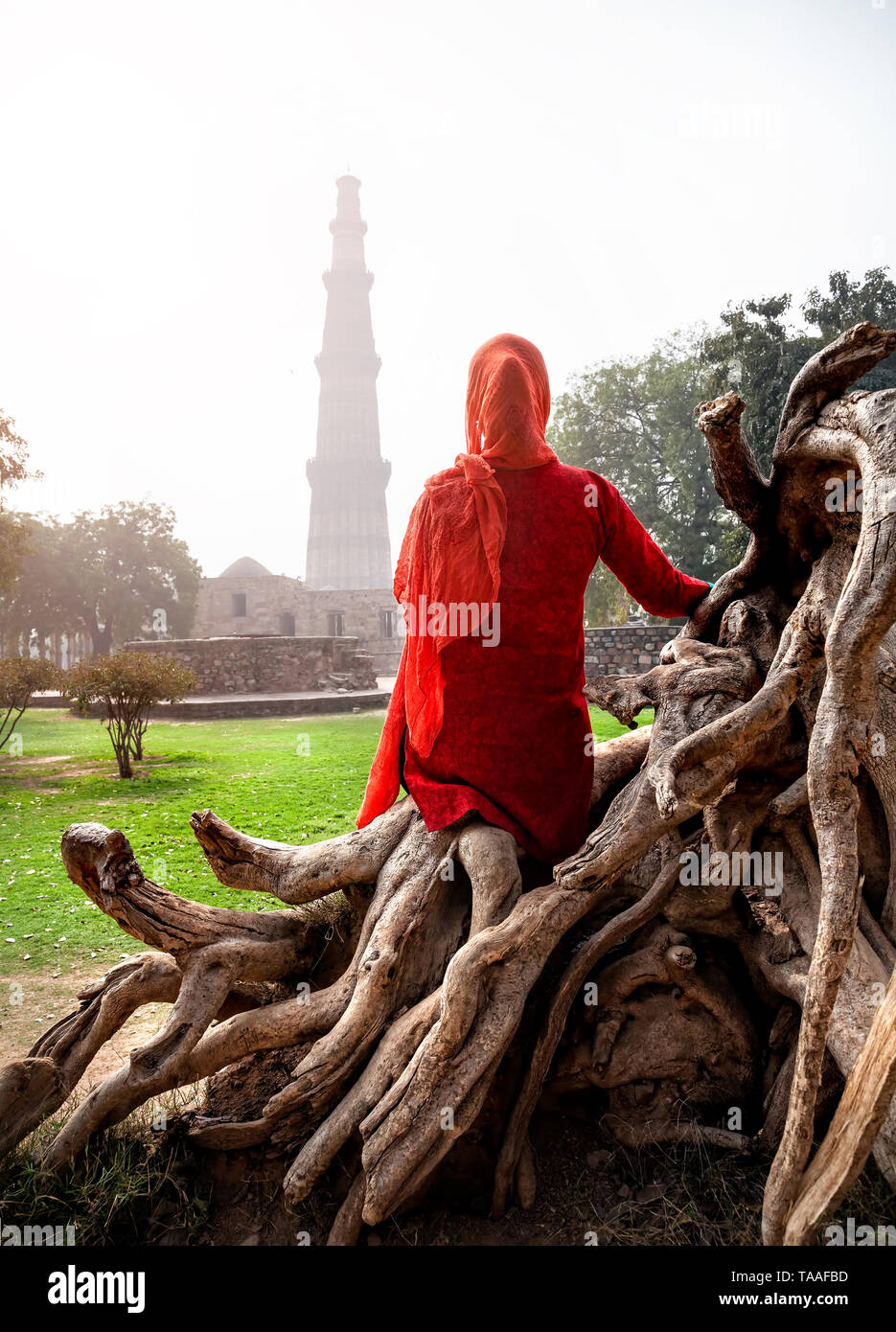 Woman in red costume sitting on the stump and looking at Qutub Minar tower in Old Delhi, India - Stock Image
