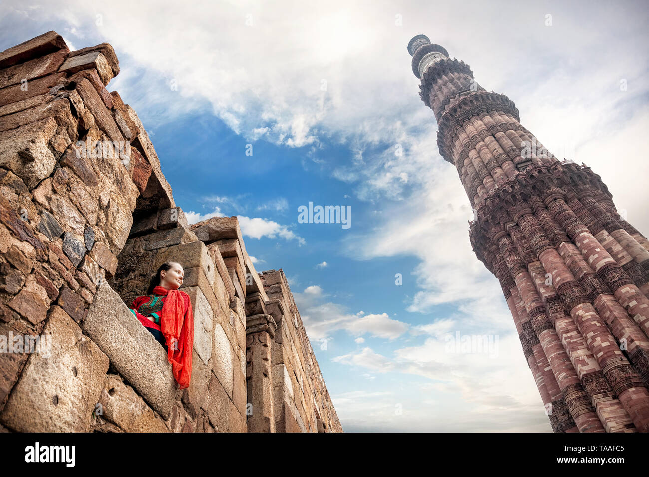 Woman in red costume sitting in the window and looking at Qutub Minar tower in Old Delhi, India - Stock Image
