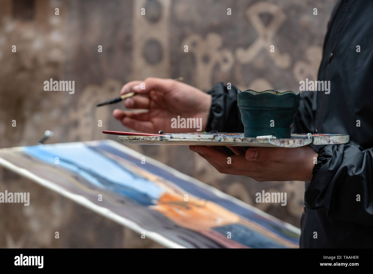 Artists hand with brush and palette painting street scene - Stock Image