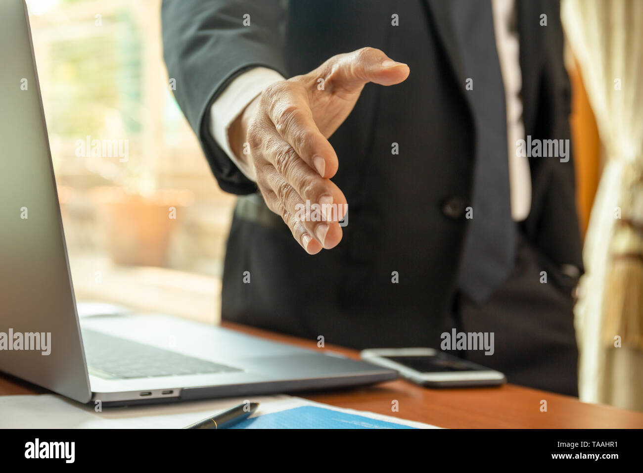 Businessman standing and reaching out hand for shaking. Stock Photo