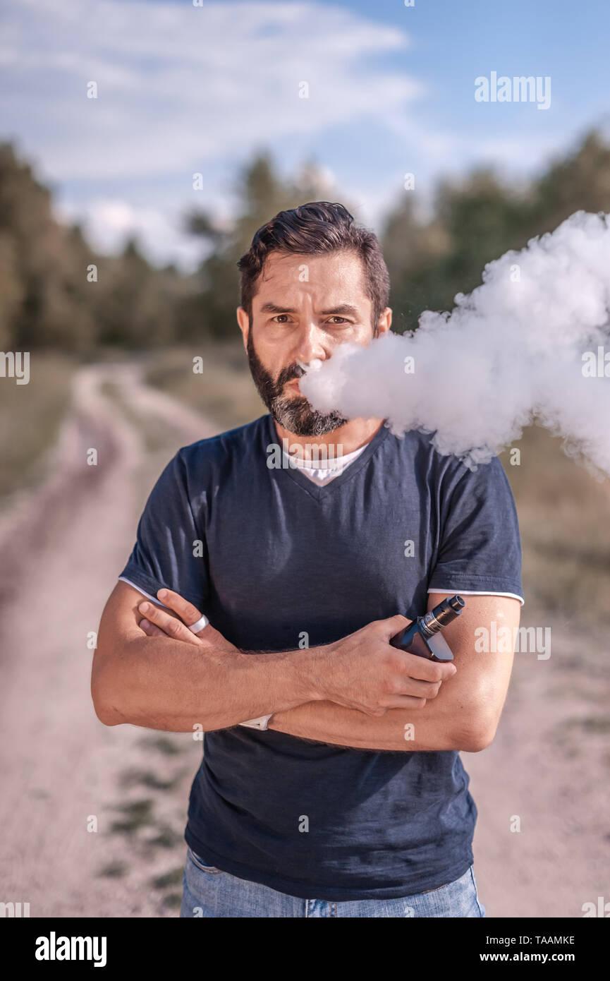 Handsome smoker vaping an electronic cigarette. Stylish man. - Stock Image