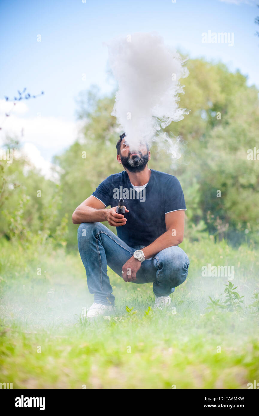 Confident man blows up a couple an e-cigarette. Getting rid of nicotine addiction. - Stock Image