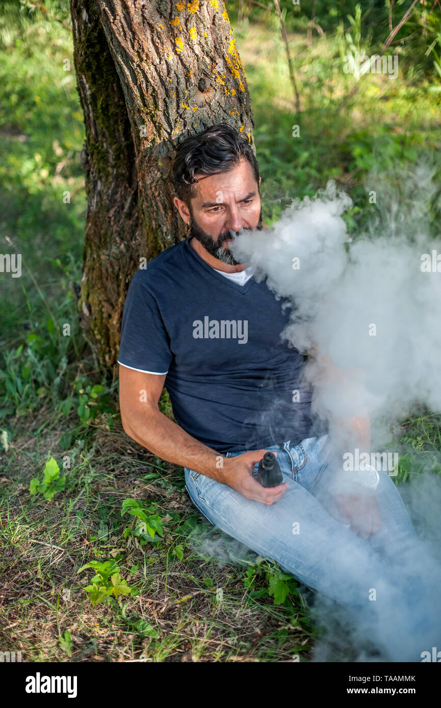 Confident man releases a cloud of steam. Electronic cigarette concept. - Stock Image