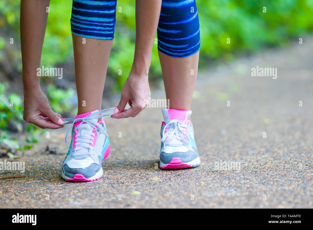 Close-up on shoe of athlete runner woman feet running on road  - Stock Image