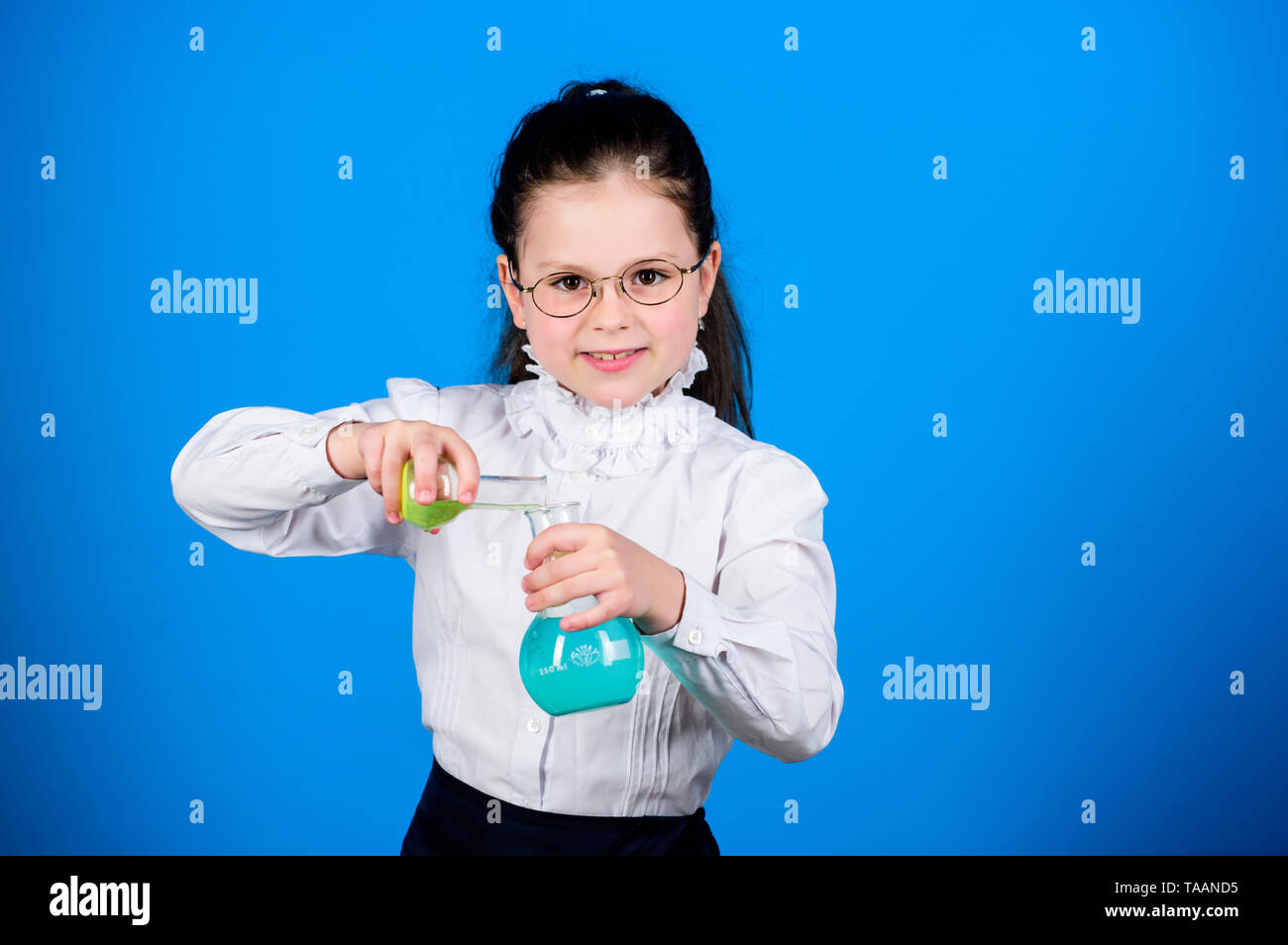 Experimenting a bit. Small kid study. Education concept. Basic knowledge. Knowledge day. Serious about studying. Schoolgirl with chemical liquids. Chi - Stock Image