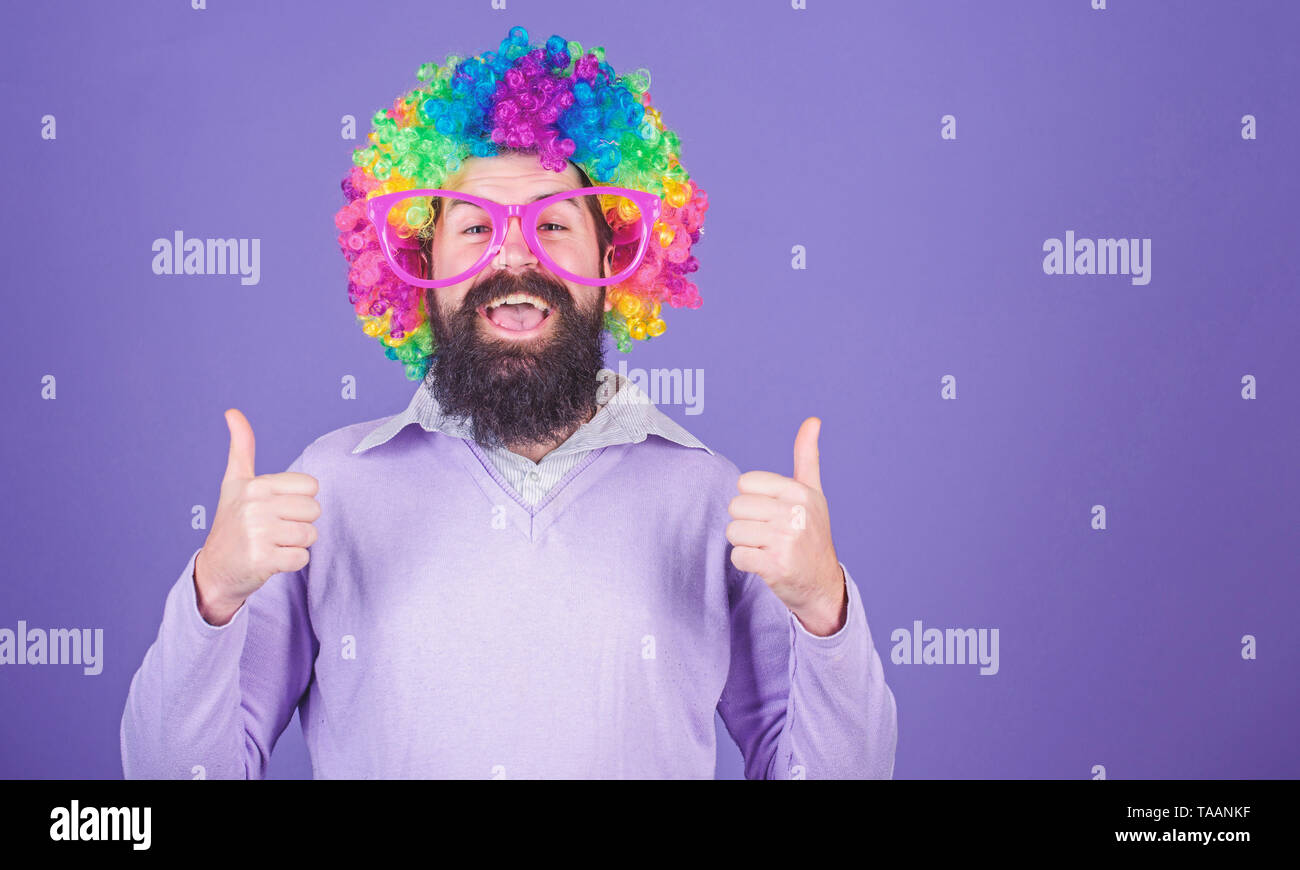 Dressed up for birthday party. Man in fashion wig gesturing thumbs up. Bearded man in clown wig hairstyle. Hipster man wearing rainbow wig hair. Happy man with long beard and curl wig, copy space. Stock Photo