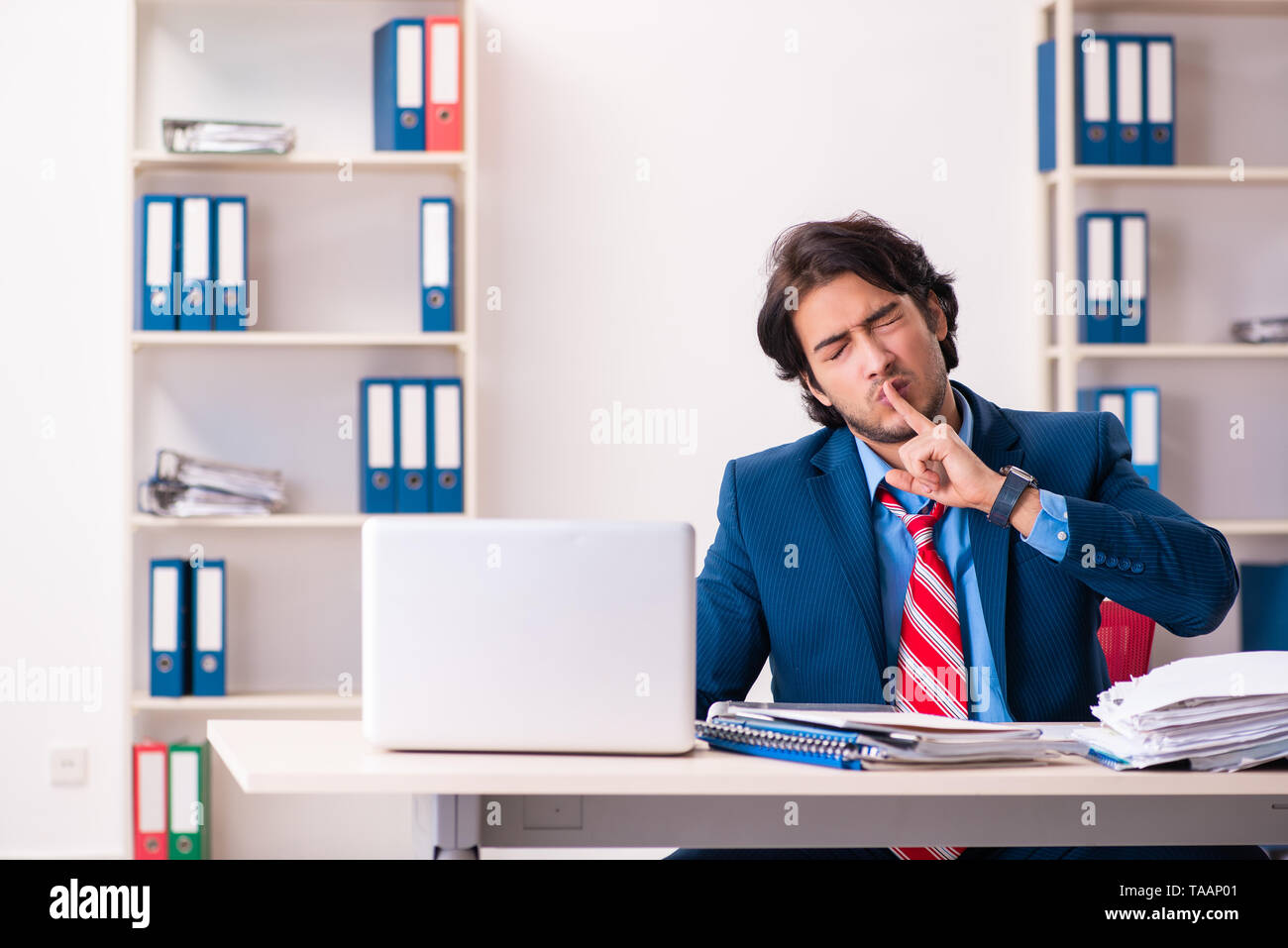 Young handsome businessman sitting in the office - Stock Image