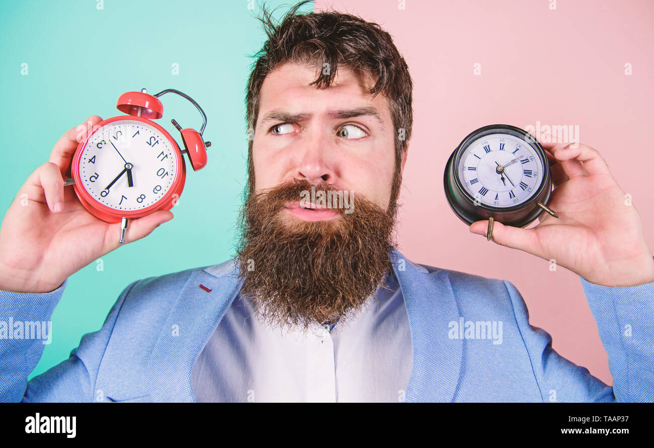 Guy unshaven puzzled face having problems with changing time. Changing time zones affect health. Time zone. Does changing clock mess with your health. Man bearded hipster hold two different clocks. - Stock Image