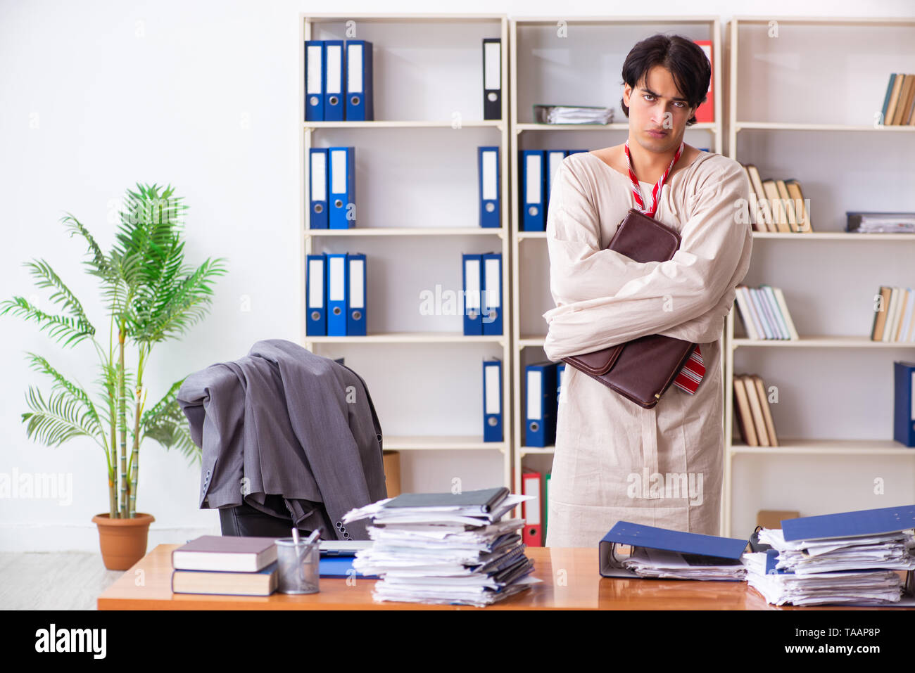 Crazy young man in straitjacket at the office - Stock Image