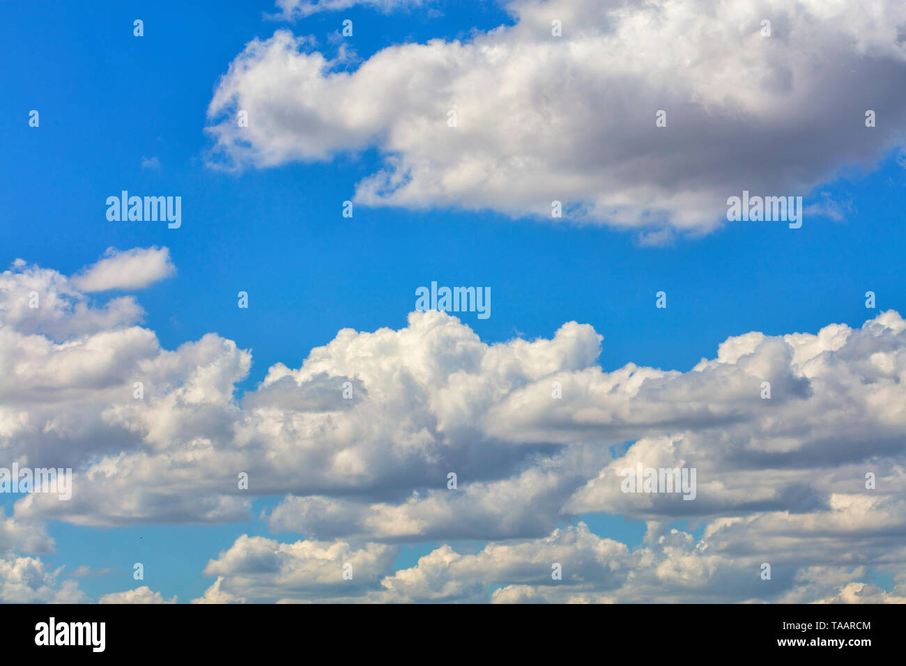 Cloudy blue sky with white and gray fluffy clouds. - Stock Image