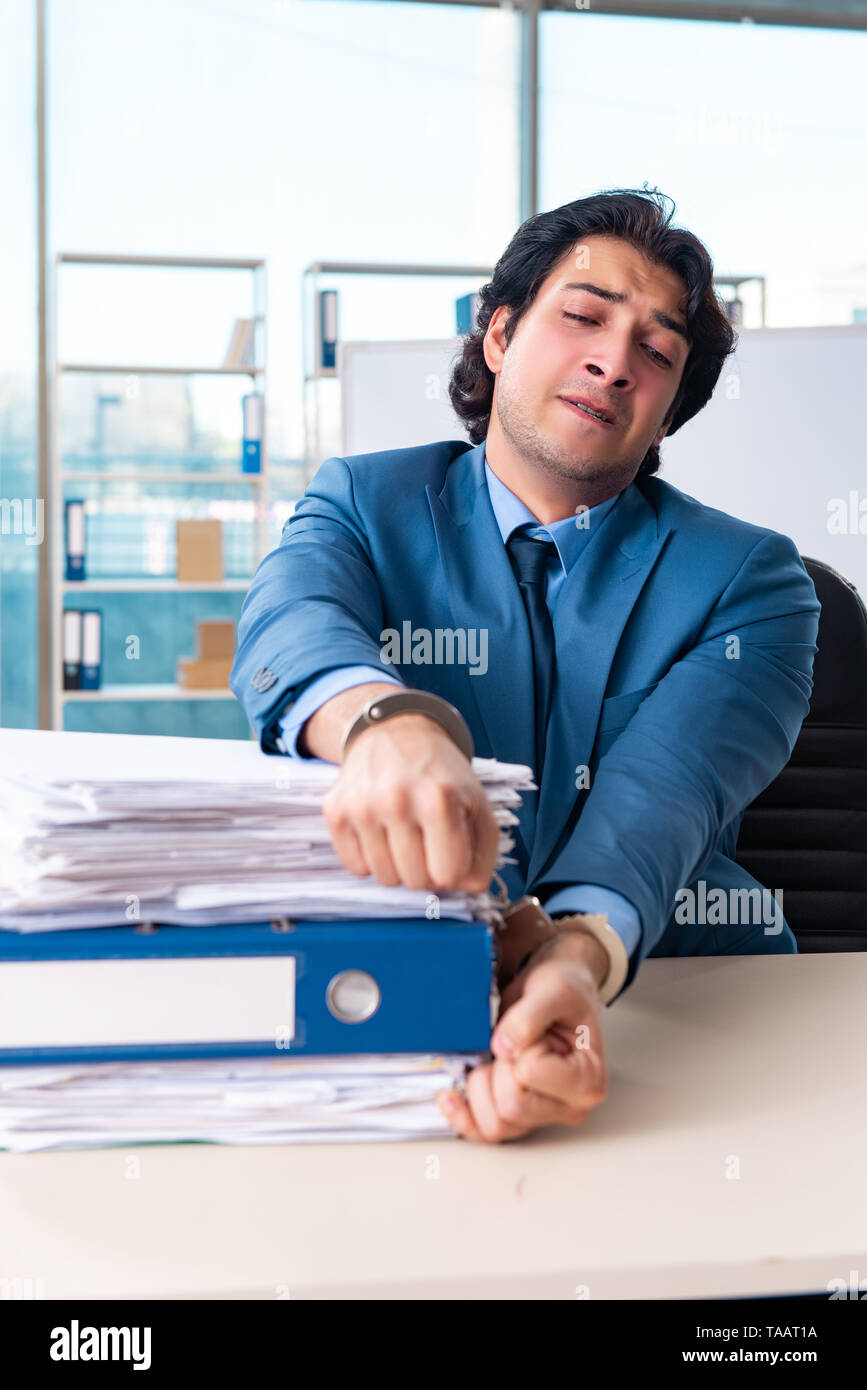 Chained male employee unhappy with excessive work - Stock Image