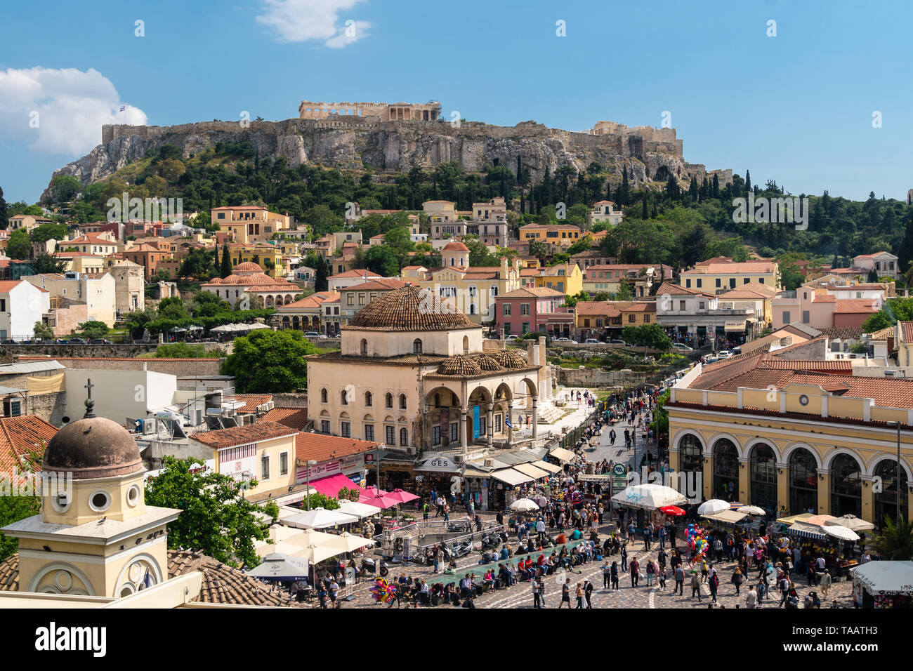 Athens, Greece - May 5 2019: Large crowd wandering around the Monastiraki square in Athens old town with the Acropolis and Parthenon temple on a sunny Stock Photo