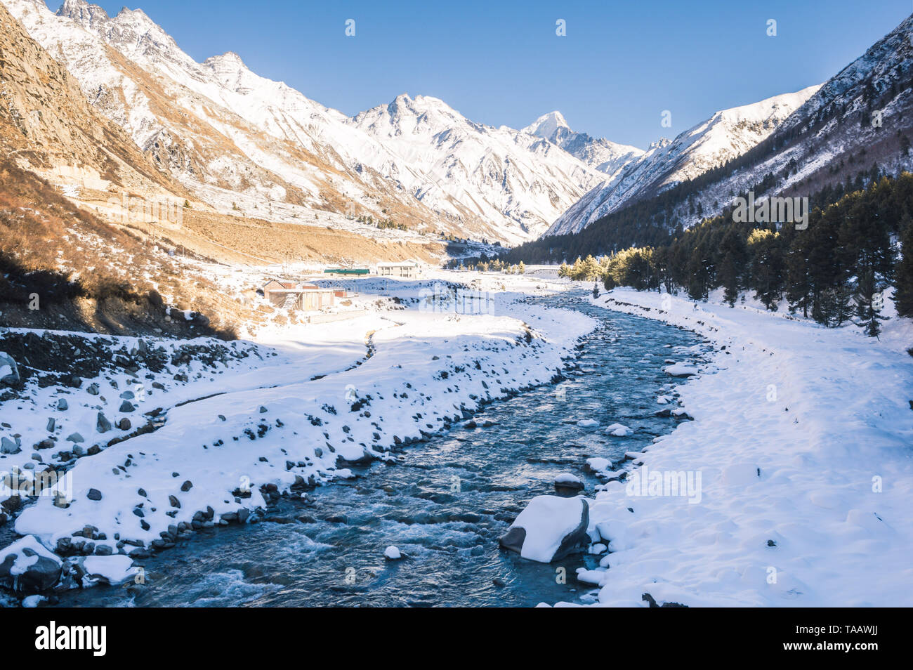 The cold and calm Baspa River flowing towards the Sangla valley through the snow-clad mountains and Chitkul, Himachal Pradesh. Stock Photo