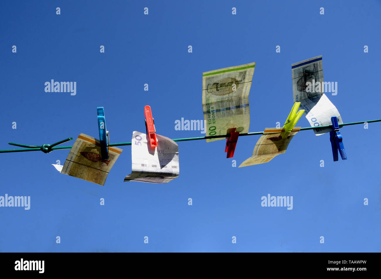 Sonderborg, Denmark - April 9, 2019: Banknotes hanging on a repaired washing line, with a blue sky as background, suggesting that money launder has ta - Stock Image