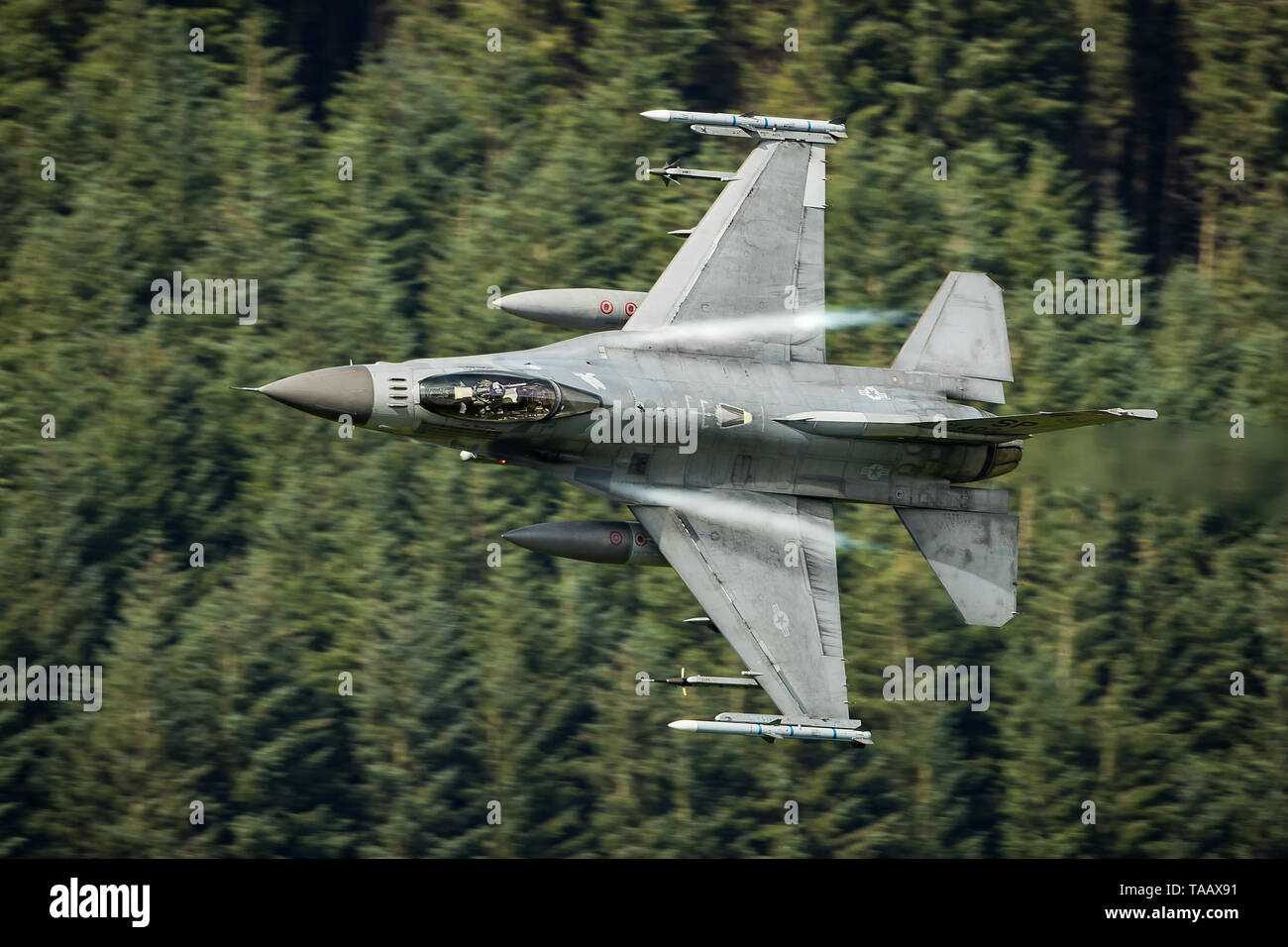 USAF F-16 fighter jet flying low level through the Mach Loop in Wales, UK Stock Photo