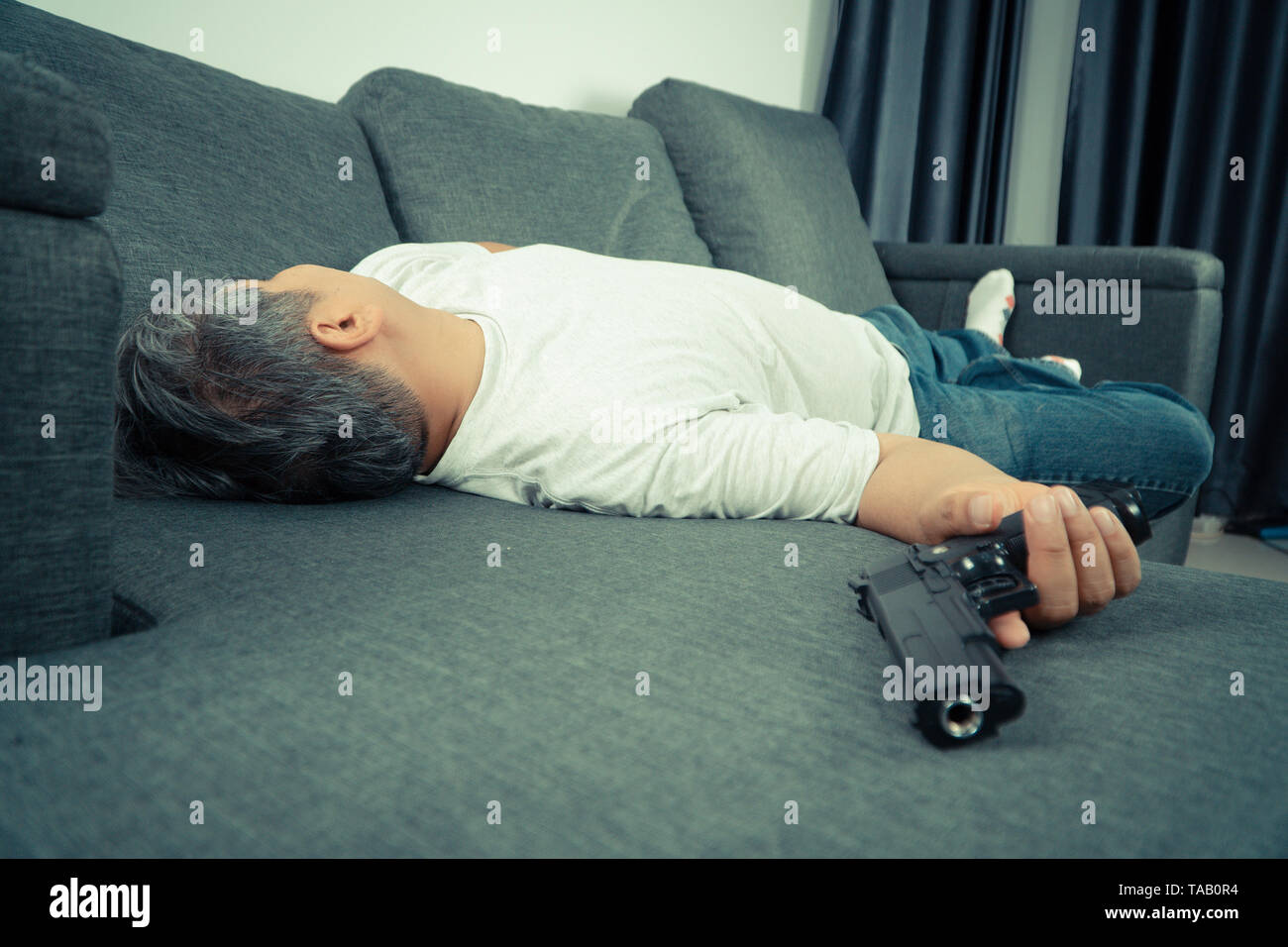 Middle-aged Asian man 40 years old hold gun in his hand and lying on the sofa in his house. Simulate the situation of people who have stress from work Stock Photo