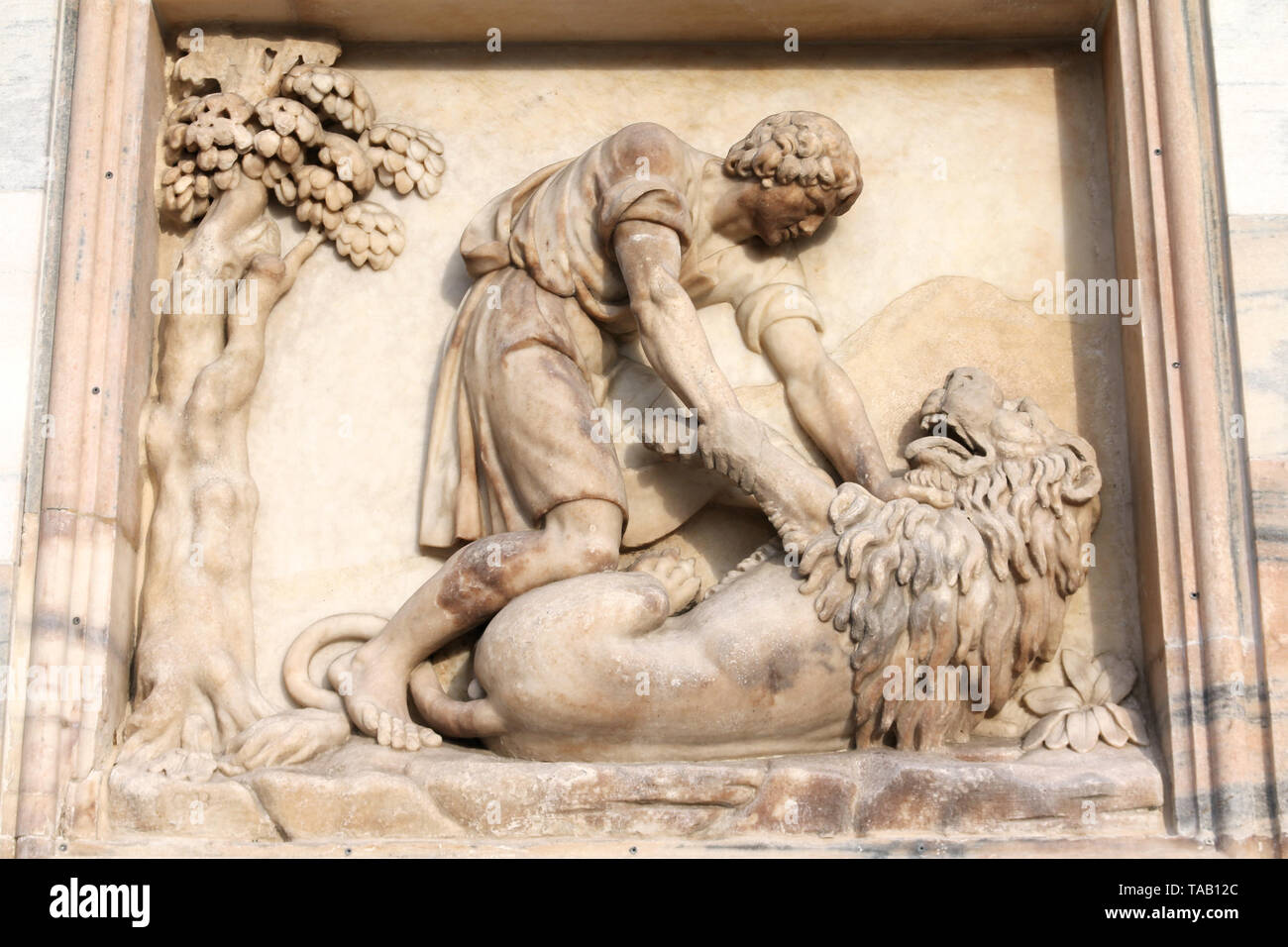 Milan, Italy. Famous landmark - the cathedral made of Candoglia marble. Samson slaying the lion - biblical story. - Stock Image