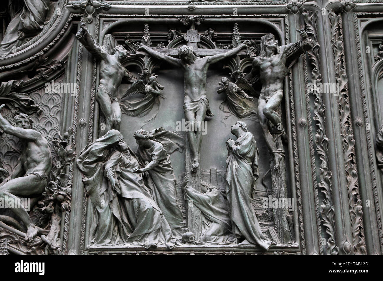 Milan, Italy. Famous landmark - the cathedral door. Jesus Christ crucified on the Cross - biblical story. - Stock Image