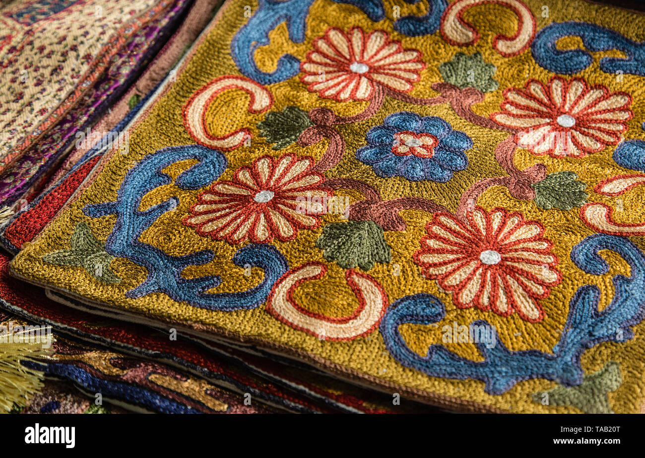 572e8bb2c Beautiful colorful handmade pashmina shawls decorated with glittering  precious stones lie on the shop counter -