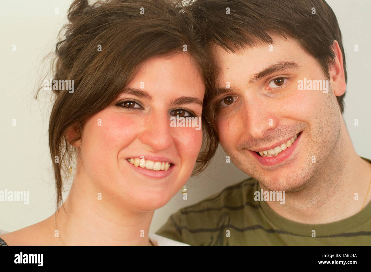 Young couple smiling and looking at the camera. Close view. - Stock Image