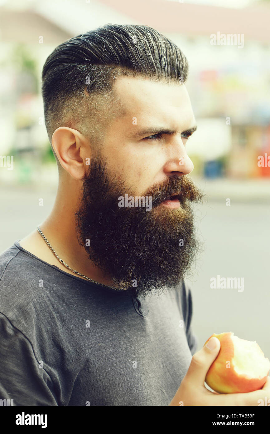 Bearded man eating apple - Stock Image