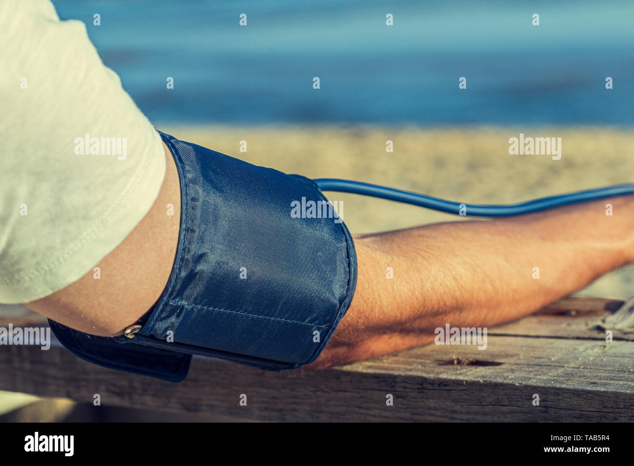 Hypertensive patient performing an automatic blood pressure test on the beach / man's self-control of blood pressure with a tensiometer on the outside - Stock Image