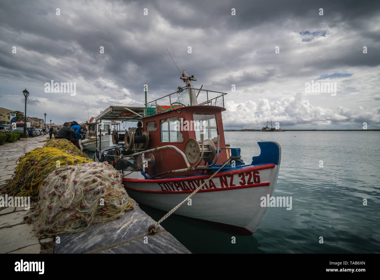 Zakynthos, Greece -  April 2019 : Large piles of nets and fishermen boat moored on the shore in Zakynthos Port, Ionian islands - Stock Image