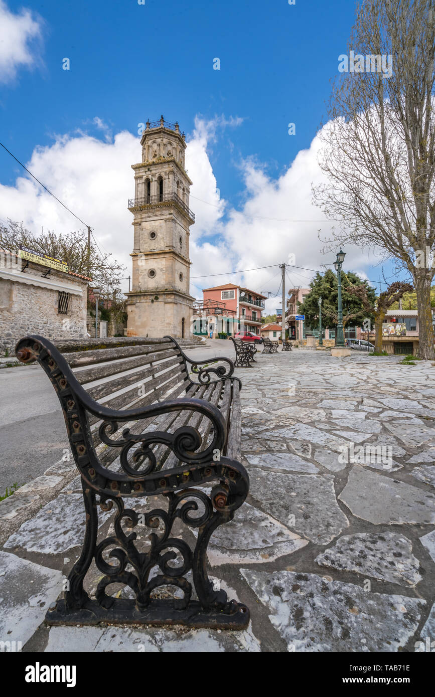 Zakynthos, Greece -  April 2019 : Empty bench in front of the bell tower of a small church in Agios Leon village - Stock Image
