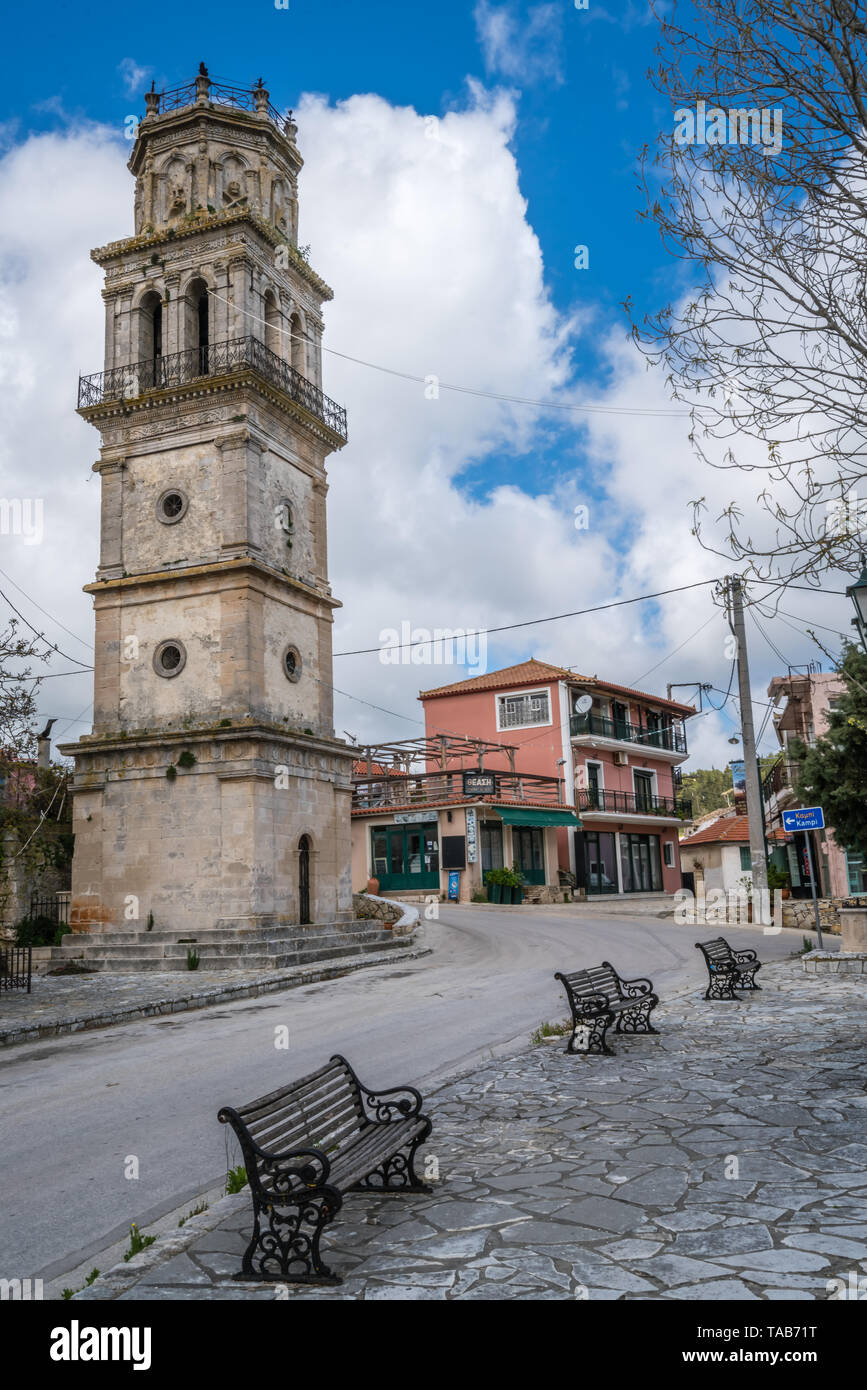 Zakynthos, Greece -  April 2019 : Empty benches in front of the bell tower of a small church in Agios Leon village, Zante - Stock Image