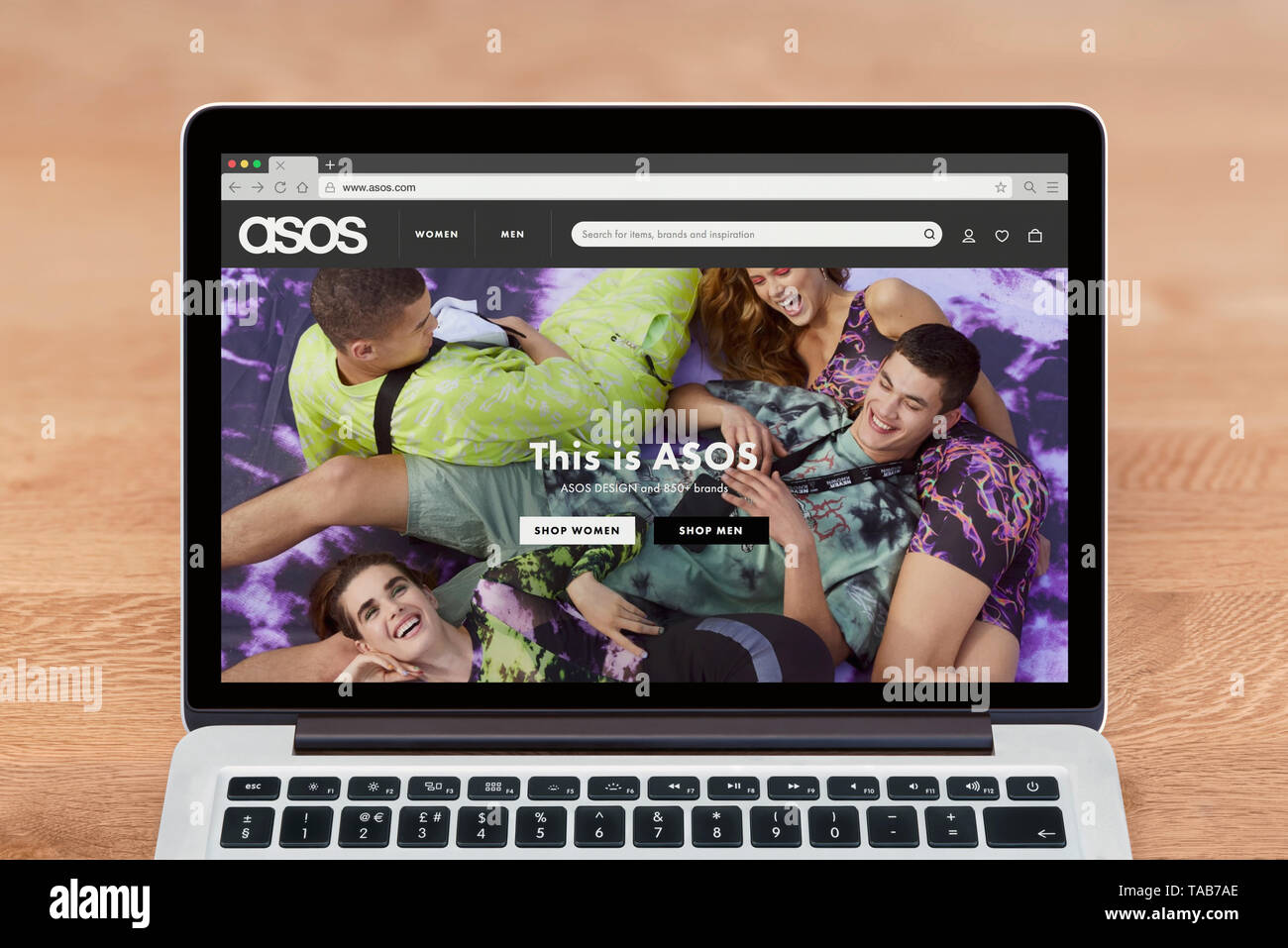 An Apple Macbook displays the Asos website (Editorial use only). - Stock Image