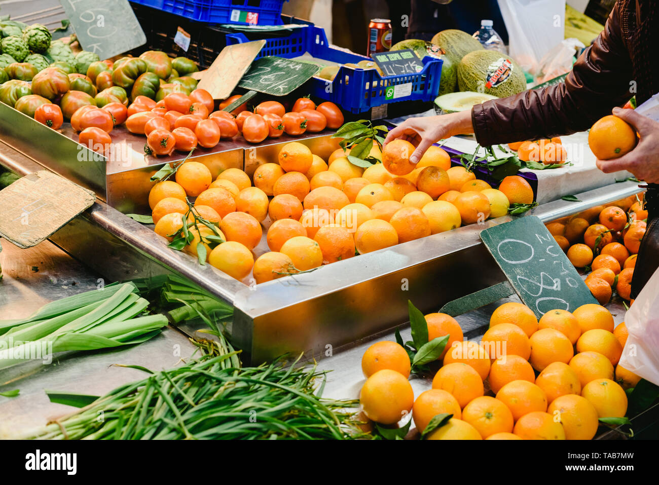 Valencia, Spain - February 2, 2019: Woman picking oranges from a fruit stall in a market . - Stock Image