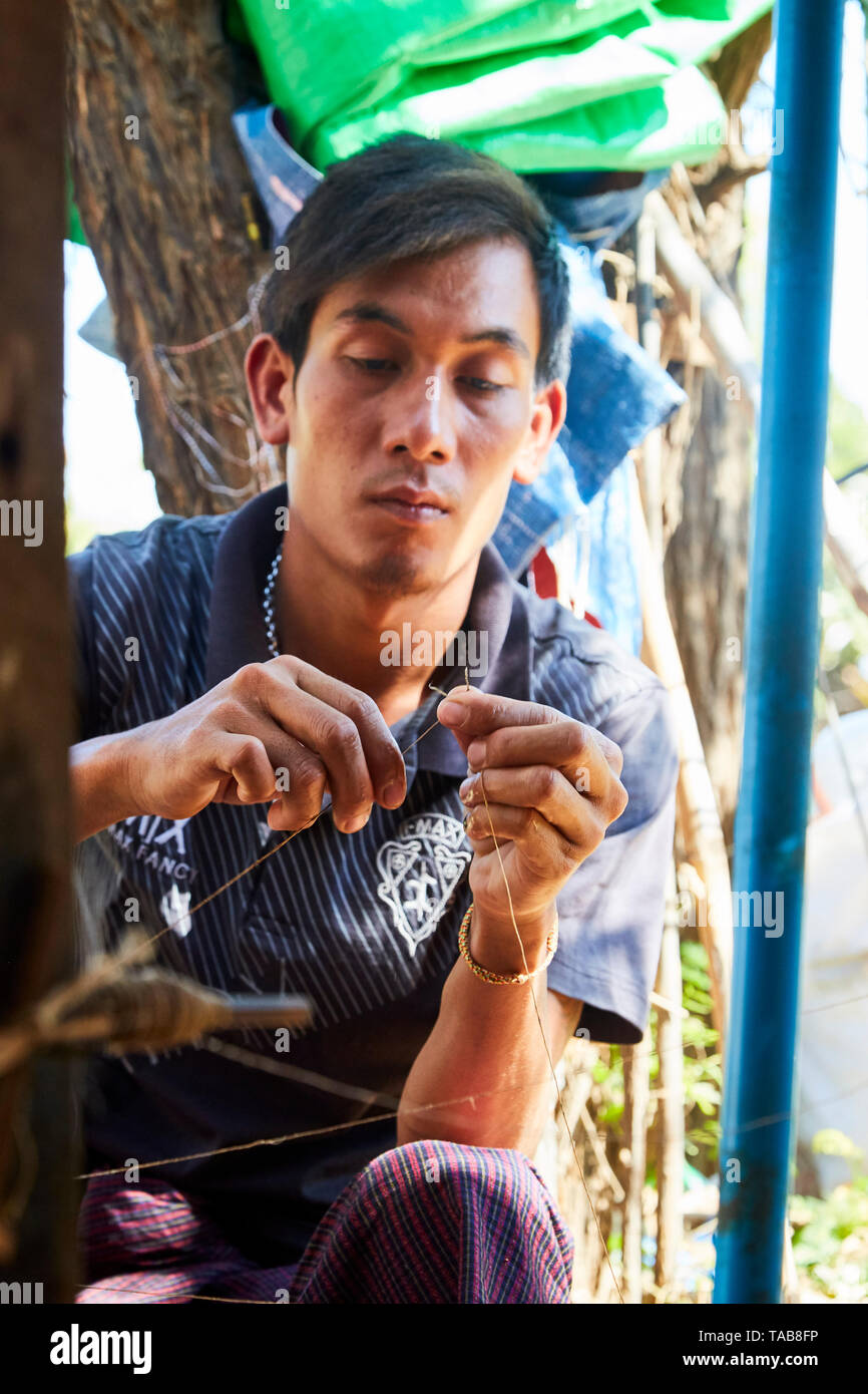 Man working  on making thread from palm leaves in craft shop in Myanmar. - Stock Image