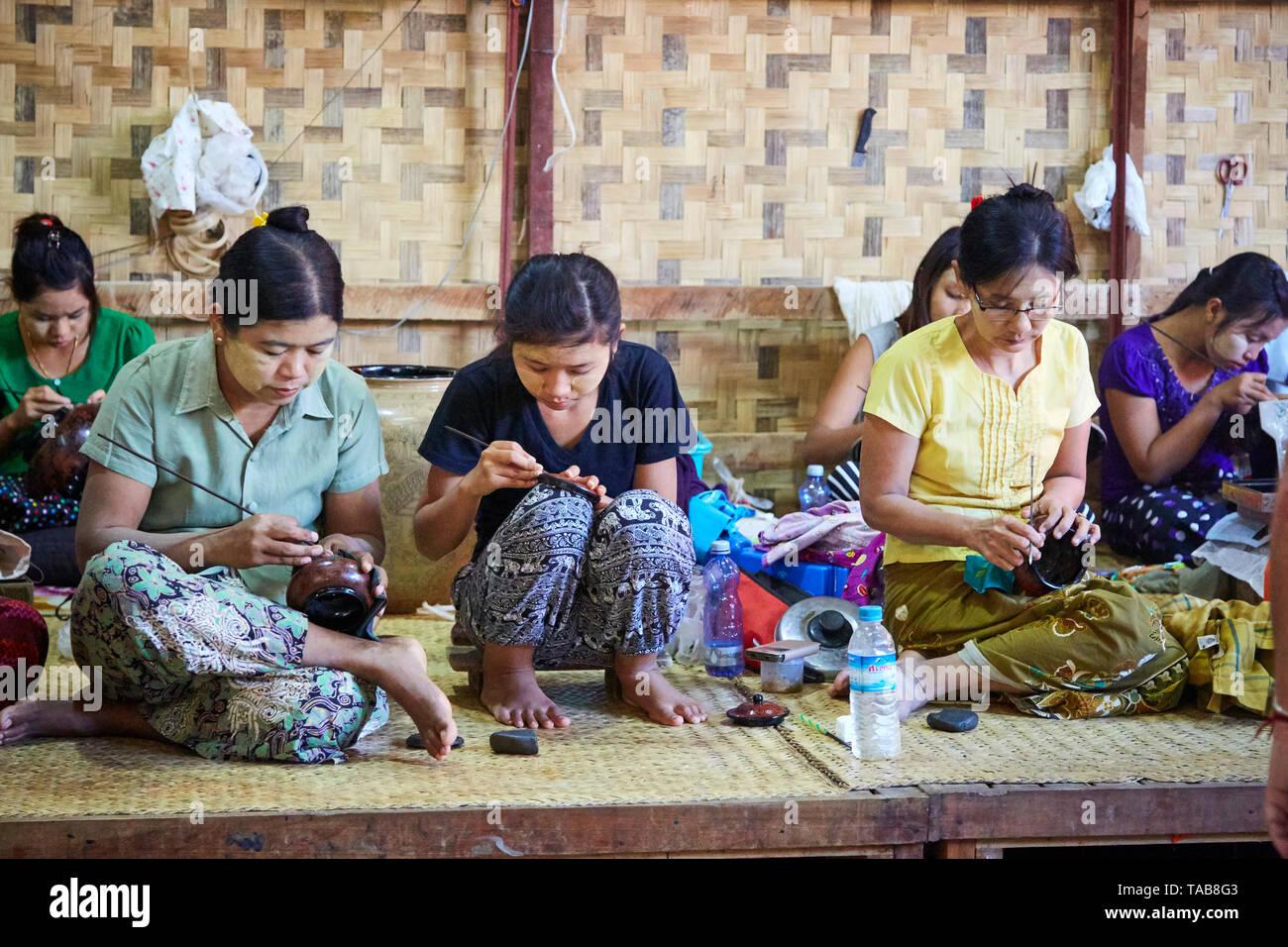 Women working etching designs into enamelware in marketplace in Bagan, Myanmar. - Stock Image