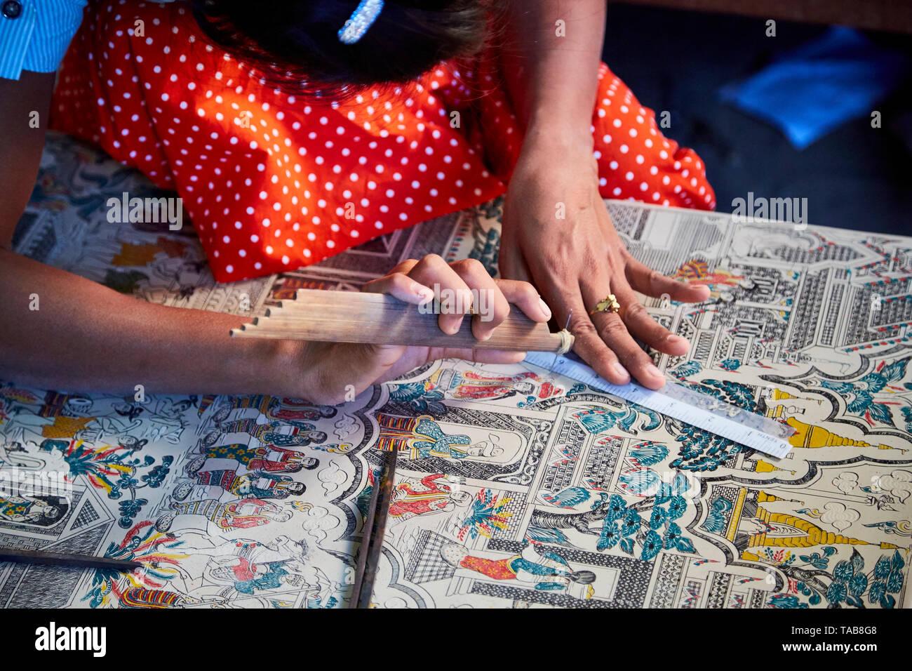 Woman working etching designs into enamelware in marketplace in Bagan, Myanmar. - Stock Image