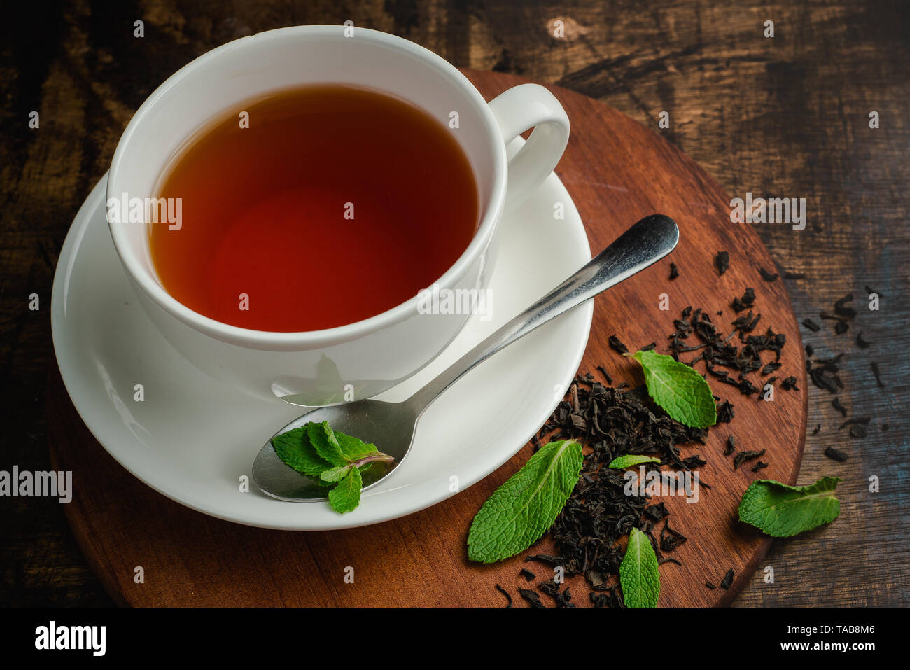 Mint tea in white porcelain cup on a warm wooden background with tea brew and mint leaves. Drink photo with copy space Stock Photo