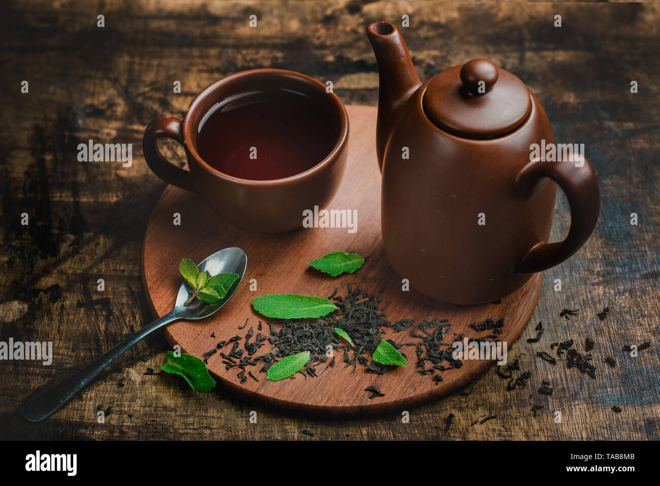 Mint tea in brown ceramic cup and teapot on a warm wooden background with tea brew and mint leaves. Stock Photo