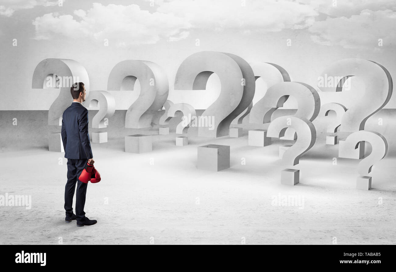 Businessman standing and looking to a bunch of question mark signs  - Stock Image