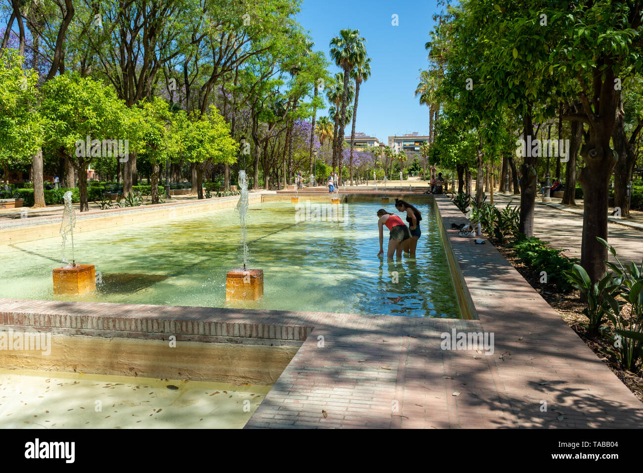 Two young women cooling down on a hot day paddling in low level fountain and water features, Prado de San Sebastian, Seville, Andalusia region, Spain - Stock Image