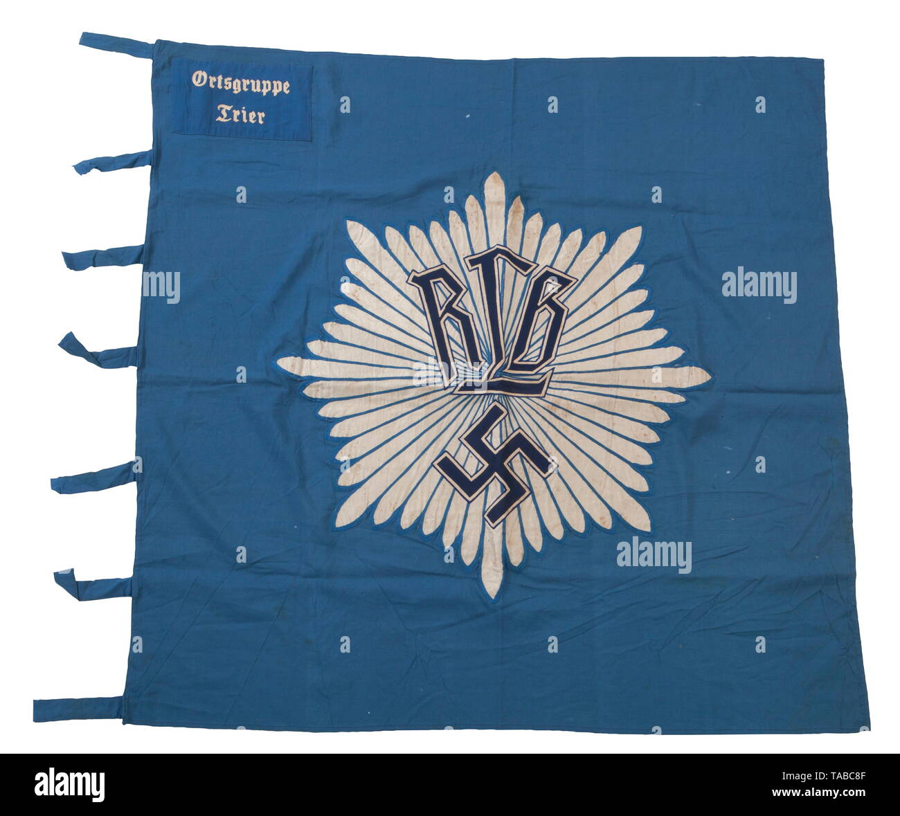 """An RLB unit flag, 1st pattern Double-sided, multi-piece, blue cotton construction. Navy blue cotton """"RLB"""" and swastika superimposed over chain stitched applied woven silver flat wire starburst rays mounted. Blue wool corner panel with white chain stitched """"Ortsgruppe Trier"""". Seven cloth attachment straps. Small holes and light staining. Approximately 120 x 120 cm. USA-lot, see page 4. historic, historical, Reichsluftschutzbund, State Air Protection Corps, organisation, organization, organizations, organisations, NS, National Socialism, Nazism, Third Reich, German Reich, Ger, Editorial-Use-Only Stock Photo"""